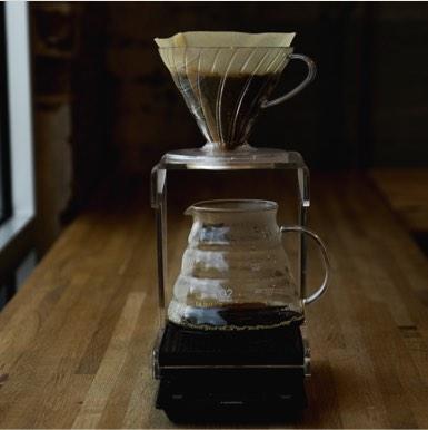 Office coffee maker on wood bar near window.