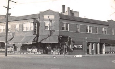 Black and white photo of historic building on street corner.