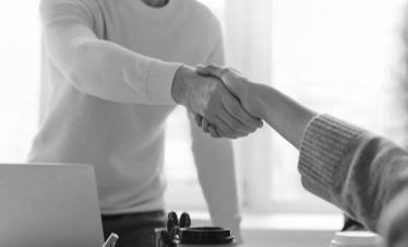 Two people shaking hands in an office.
