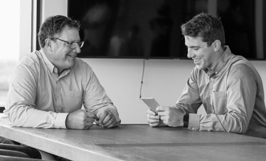 Two men in white collar shirts sitting at an office table, smiling.